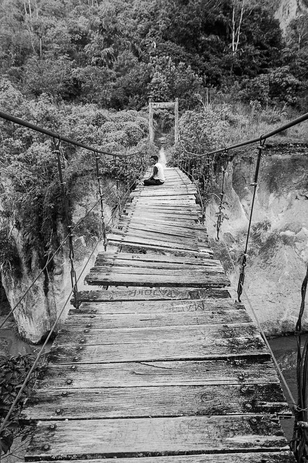 Photographie de voyage - homme méditant sur un pont suspendu, Indonésie