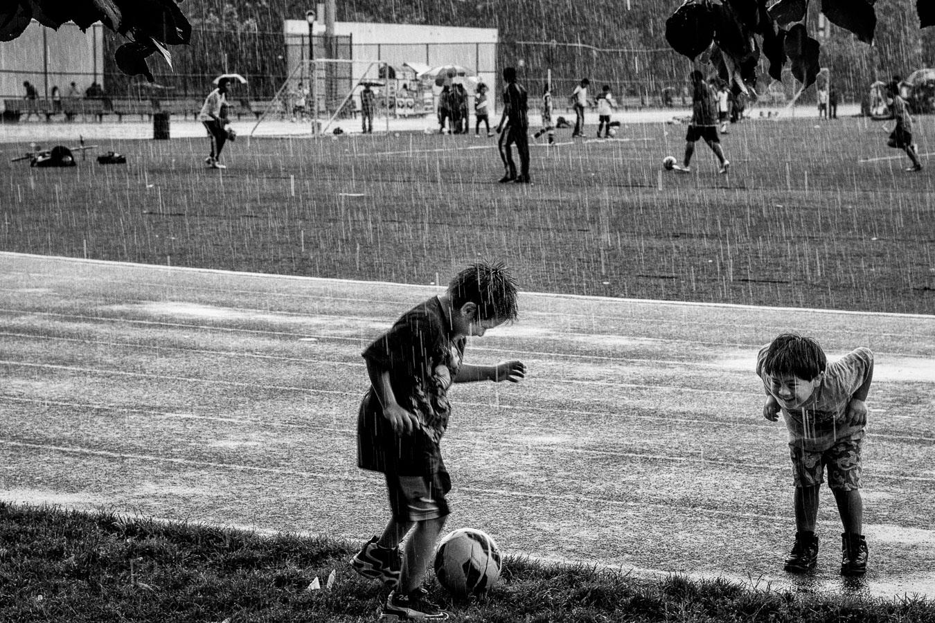 Photographie de voyage - jeunes enfants jouant au foot sous la pluie, New York